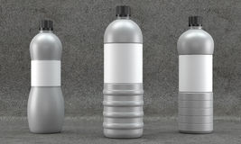 Plastic bottles mockup on concrete background. Different shaped non transparent plastic bottles mockups on concrete background Royalty Free Stock Image