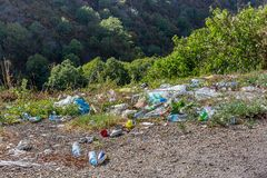 Plastic bottles and other trash along the mountain road. A lot of trash at roadside. Concept of environmental pollution royalty free stock images