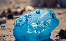 Plastic bottles in a plastic bag. Plastic waste bottles in plastic bag thrown into a beach royalty free stock image