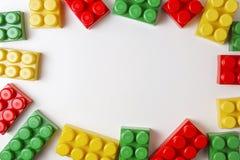 Plastic bouwblokken op witte achtergrond als kader van het jonge geitjesspeelgoed met exemplaarruimte voor tekst Vlak leg Hoogste Stock Afbeeldingen