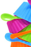 Plastic bowls. And spoons of different colors on a white background Stock Images