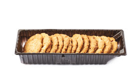 Plastic box filled with cookies isolated. Plastic box filled with oatmeal thin cookies isolated over the white background Royalty Free Stock Photography