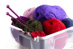 Plastic box with knitting needles and wool. Plastic box with knitting needles and balls of grey, blue, lilac and red wool or yarn  on white in a concept of Royalty Free Stock Image