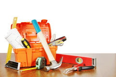 Plastic box with various working tools stands on a wooden table Royalty Free Stock Photos