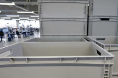 Plastic boxes in a production hall Stock Images