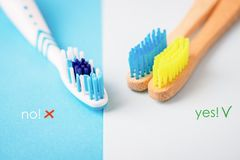 Plastic and bright bamboo toothbrushes on blue and white background. Alternative concept. Toothbrush selection, eco. Plastic and bamboo toothbrushes on blue and stock image