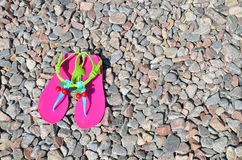 Plastic bright flip-flops on the pebble Royalty Free Stock Photography