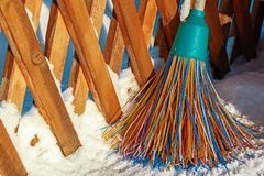 A plastic broom with multicolored bristles of the pile stands in the snow. The concept of cleaning  the area of snow in the winter. Close-up of the object with royalty free stock images