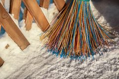 A plastic broom with multicolored bristles of the pile stands in the snow. The concept of cleaning  the area of snow in the winter. Close-up of the object with royalty free stock photo