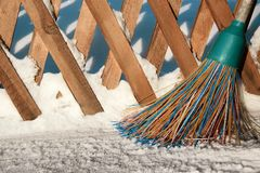 A plastic broom with multicolored bristles of the pile stands in the snow. The concept of cleaning  the area of snow in the winter. Close-up of the object with royalty free stock image