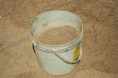 Plastic bucket with sand in a construction site. Plastic bucket with sand in construction site of an old house, in a sunny day at Castelo de Vide. Nice little royalty free stock image