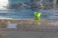 The plastic bucket which costs. On edge of pool Royalty Free Stock Images