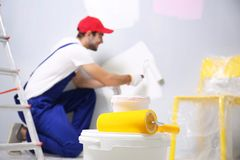 Plastic buckets and paint roller with blurred worker. On background Royalty Free Stock Images