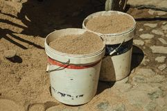 Plastic buckets with sand in construction site. Of an old house, on sunny day at Castelo de Vide. Nice little town with medieval castle to ensure the defense of stock images