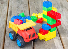 Plastic building blocks and toy truck. On a wooden background Stock Images