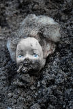 Plastic burnt doll head lying in a pile of ash Stock Image