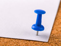 The plastic button with a needle stuck in an iron sheet of white Royalty Free Stock Photo