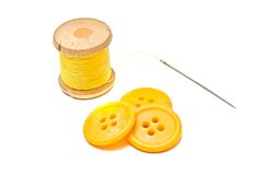 Plastic buttons and spool of yellow thread Stock Photo