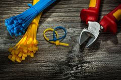 Plastic cables cutting pliers on vintage wooden board royalty free stock images