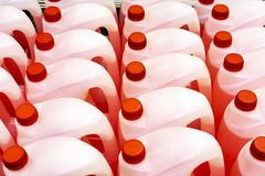 Plastic canisters with red liquid on the shop counter royalty free stock photography