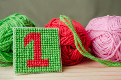 Plastic Canvas, hand made with red yarn number on wooden backgro. Und Royalty Free Stock Photo