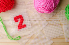 Plastic Canvas, hand made with red yarn number on wooden backgro. Und Royalty Free Stock Photos