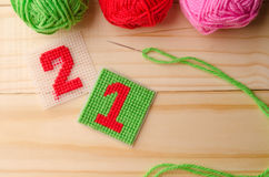 Plastic Canvas, hand made with red yarn number on wooden table. Plastic Canvas, hand made with red yarn number on wooden background Stock Images