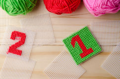 Plastic Canvas, hand made with red yarn number on wooden table. Plastic Canvas, hand made with red yarn number on wooden background Stock Photography