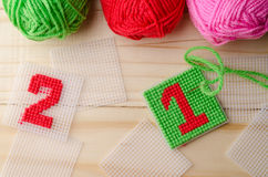 Plastic Canvas, hand made with red yarn number on wooden table. Plastic Canvas, hand made with red yarn number on wooden background Royalty Free Stock Photography