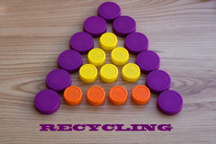 Plastic caps in the form of a triangle, as a background. Plastic capss from PET bottles, for recycling Stock Photos