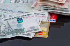 Plastic card payment systems Visa and MasterCard. VOLGOGRAD - AUGUST 16: Plastic card payment systems Visa and MasterCard are with a bunch of Russian money Stock Photography
