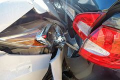 Rear end collision of two cars, one black, the other white. Plastic cars crumbling in a collision, the front end of the white car, the rear end of the black one royalty free stock photo