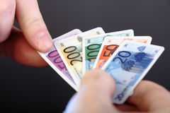 Plastic cash. Man choosing Five Hundred Euro Banknote, but plastic, fake money, toy Royalty Free Stock Photo