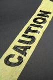 Plastic caution tape. Yellow plastic caution tape with dark background Stock Photos