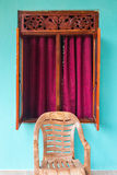 Plastic chair in front of the opened window. Plastic chair in front of the opened window with wooden decoration and cyclamen curtains Royalty Free Stock Photos