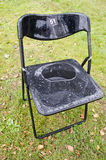 Plastic chair on park grass after rain with drops Stock Image