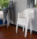 Plastic chairs. A picture of two stacks of plastic chairs, placed outside a building Stock Image