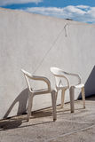 Plastic chairs alone. Plastic chairs on a concrete roof top terrace, in hard sun light Royalty Free Stock Images