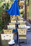 Plastic Chairs and Blue Umbrella at Restaurant Patio Stock Photos