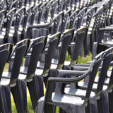 Plastic chairs. Dark-blue plastic chairs waiting for audience at an open-air event on a green lawn stock photo