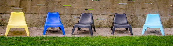 5 plastic chairs in a row. Yellow, blue, black, light blue Royalty Free Stock Photo