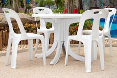 Plastic chairs and a table over a swimming pool Royalty Free Stock Image