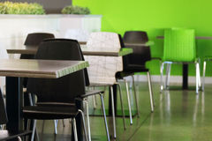 Plastic chairs and tables in empty cafe with green walls Stock Photos