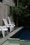 Plastic chairs. White plastic chairs standing around the swimming-pool Royalty Free Stock Photography