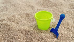 Plastic children`s toys in the sand. Concept of family vacation. Top view. Space for text. stock photography