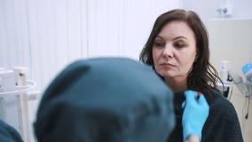 Plastic chirurg die midden oud vrouwengezicht controleren vóór kosmetische chirurgie stock video