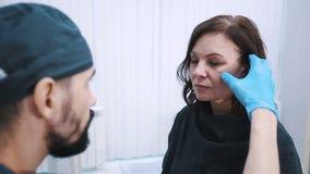 Plastic chirurg die midden oud vrouwengezicht controleren vóór kosmetische chirurgie stock footage