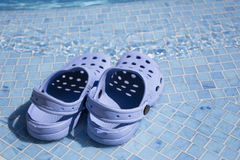 Plastic clogs near the swimming pool. Small pair of children`s rubber footwear for trips to the beach and in the pool. Specialized Shoe is on the edge of the Stock Photography
