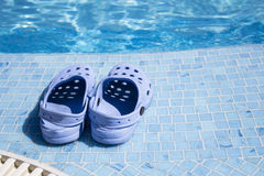 Plastic clogs near the swimming pool. Small pair of children`s rubber footwear for trips to the beach and in the pool. Specialized Shoe is on the edge of the Royalty Free Stock Image