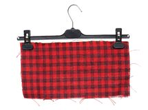 Plastic clothes hanger with hanging on it a piece of checkered. Cloth red Royalty Free Stock Photos